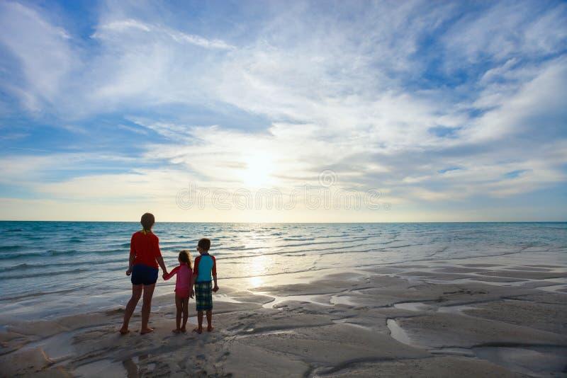 Мать и дети на силуэтах пляжа стоковые фотографии rf