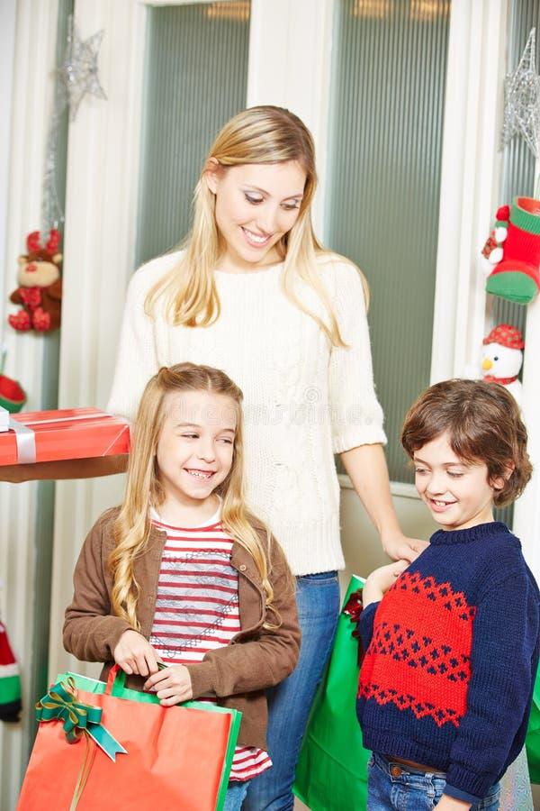 Мать и дети нося подарки рождества стоковое фото rf