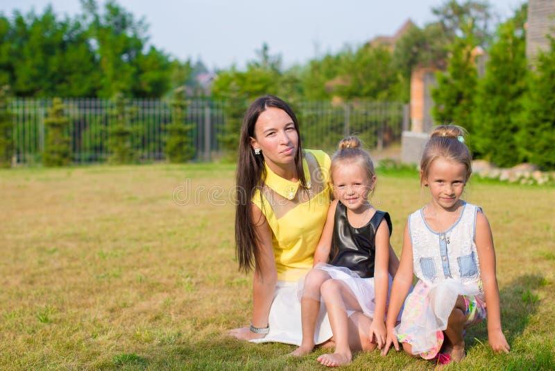 Мать и дети сидя outdoors на красивом стоковая фотография