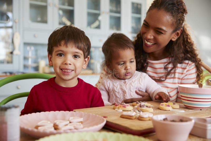 Мать и дети украшая печенья дома совместно стоковое изображение
