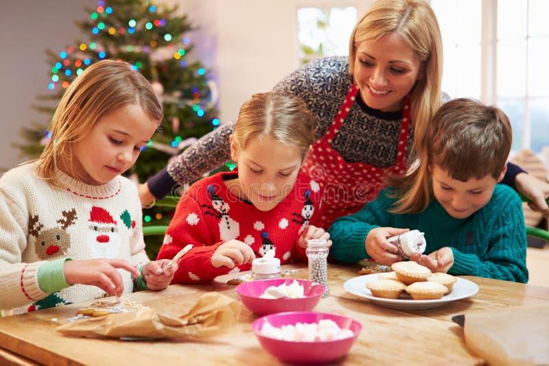 Мать и дети украшая печенья рождества совместно стоковое фото rf