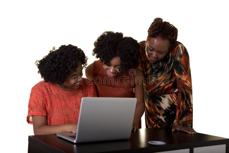 Мать или учитель смотря компьютер с 2 подростками стоковые фотографии rf