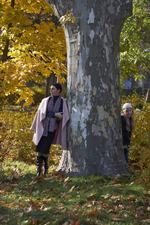 Мать и маленькая девочка пряча за деревом стоковое изображение