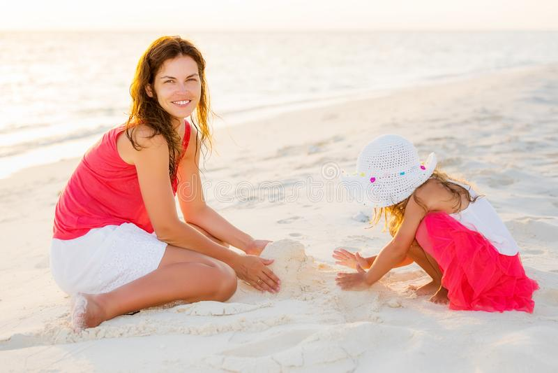 Мать и маленькая дочь играя на пляже на Мальдивах на летних каникулах стоковое фото rf