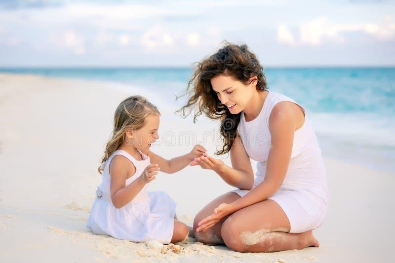 Мать и маленькая дочь играя на пляже на Мальдивах на летних каникулах стоковые изображения