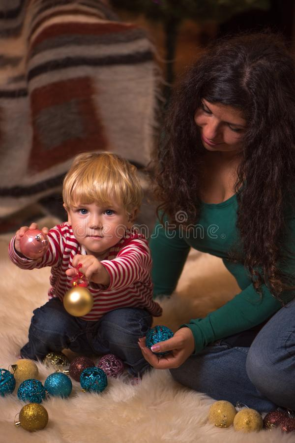 Мать и маленький малыш играя с деревом christmass клокочут стоковые фотографии rf