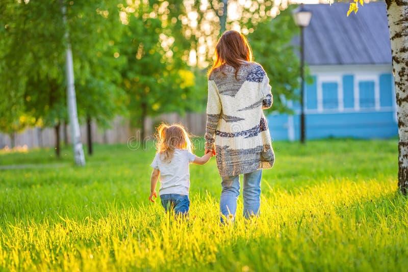 Мать и маленький парк дочери весной солнечный стоковые фотографии rf