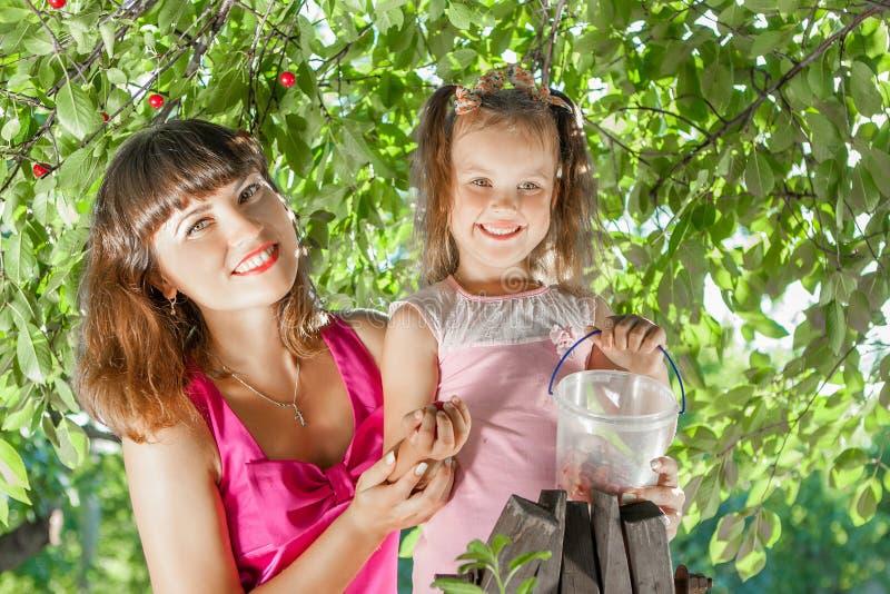 Мать и маленькая дочь в саде стоковое фото rf