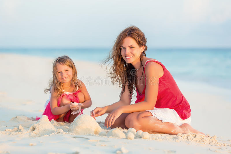 Мать и маленькая дочь играют на пляже стоковые фото