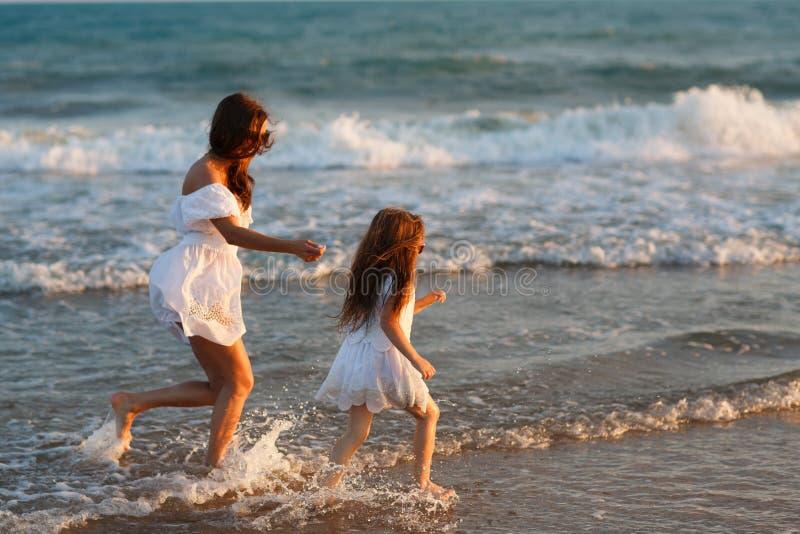 Мать и маленькая дочь имеют потеху на пляже стоковое фото rf