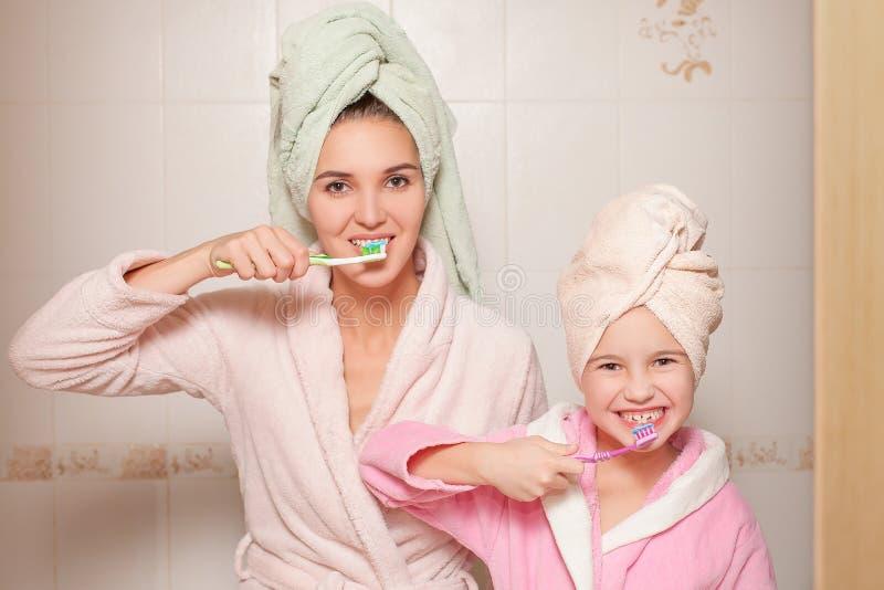 Мать и маленькая дочь с зубными щетками стоковое изображение rf