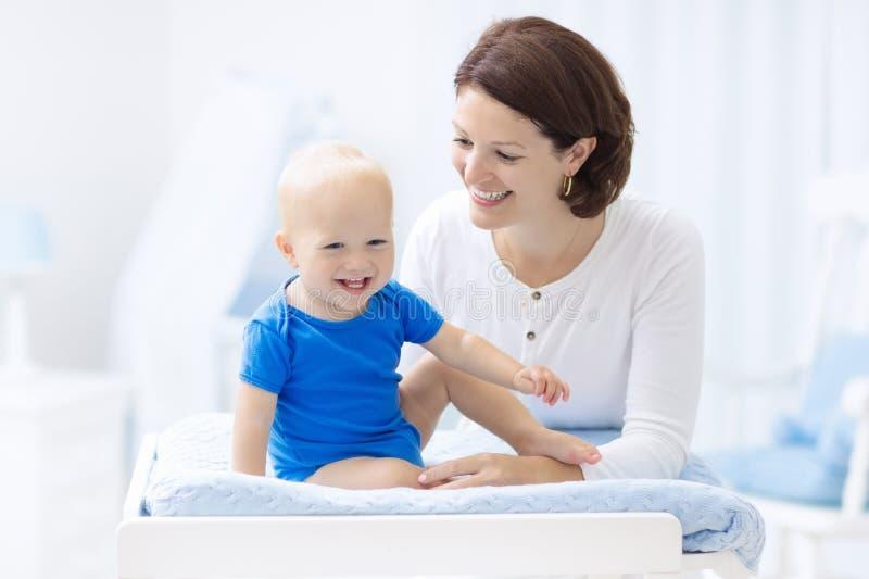 Мать и младенец на изменяя таблице стоковые фотографии rf