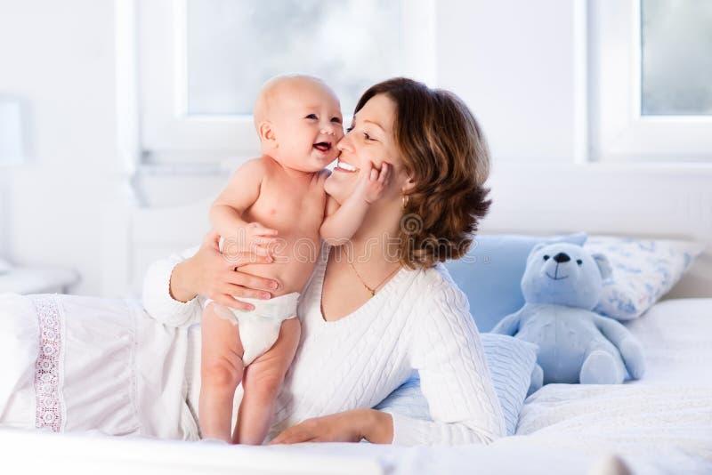 Мать и младенец на белой кровати стоковое изображение
