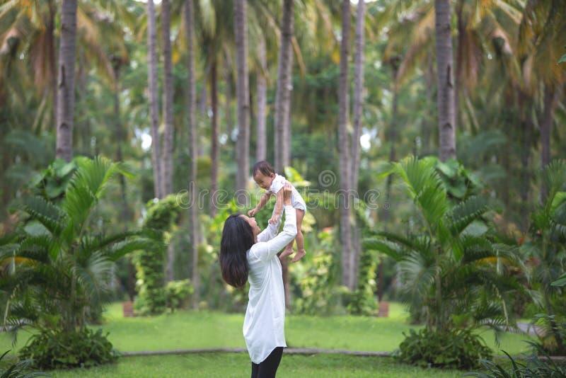 Мать и отец красоты с их newborn младенцем в парке стоковое изображение