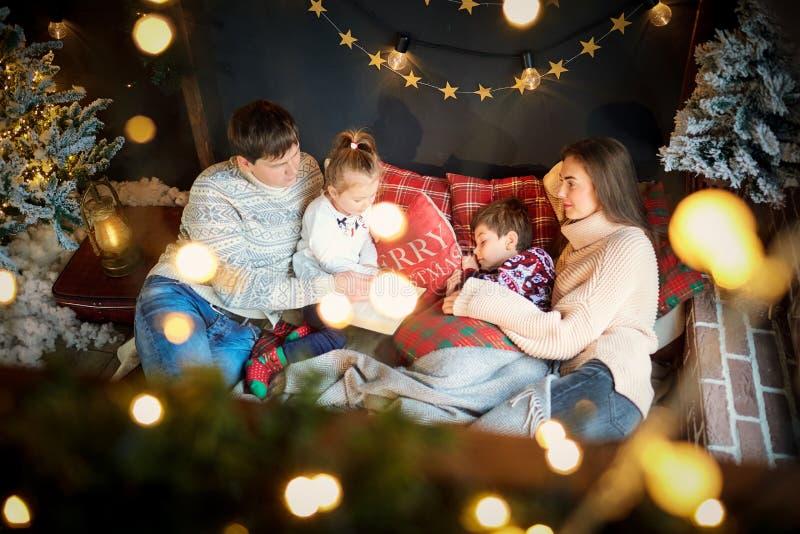 Мать и отец при дети играя дома на Рождество стоковое изображение