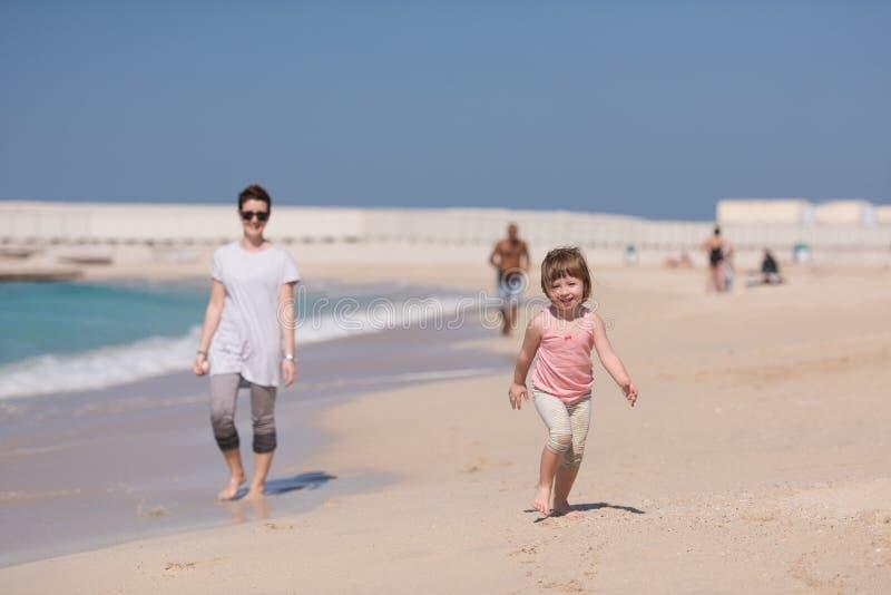 Мать и дочь бежать на пляже стоковое фото