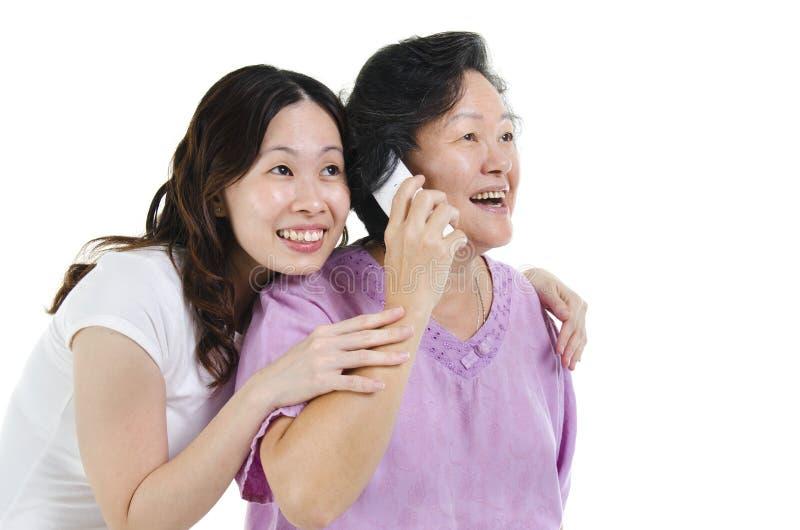 Мать и дочь вызывая на телефоне стоковое изображение