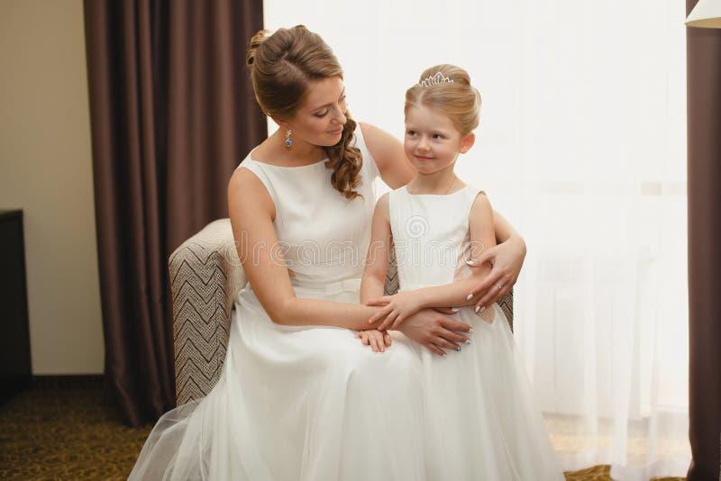 Мать и дочь в таких же платьях свадьбы стоковая фотография
