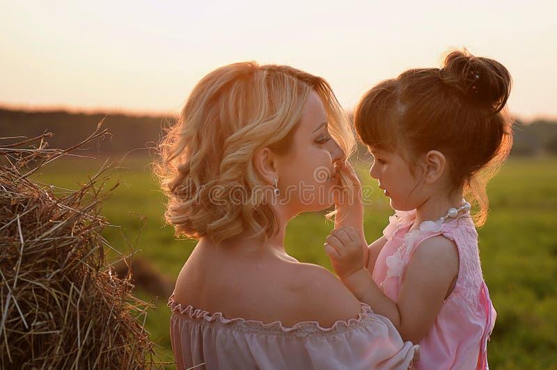 Мать и дочь в этих же вводят поле в моду, свет захода солнца Нежность стоковые фотографии rf