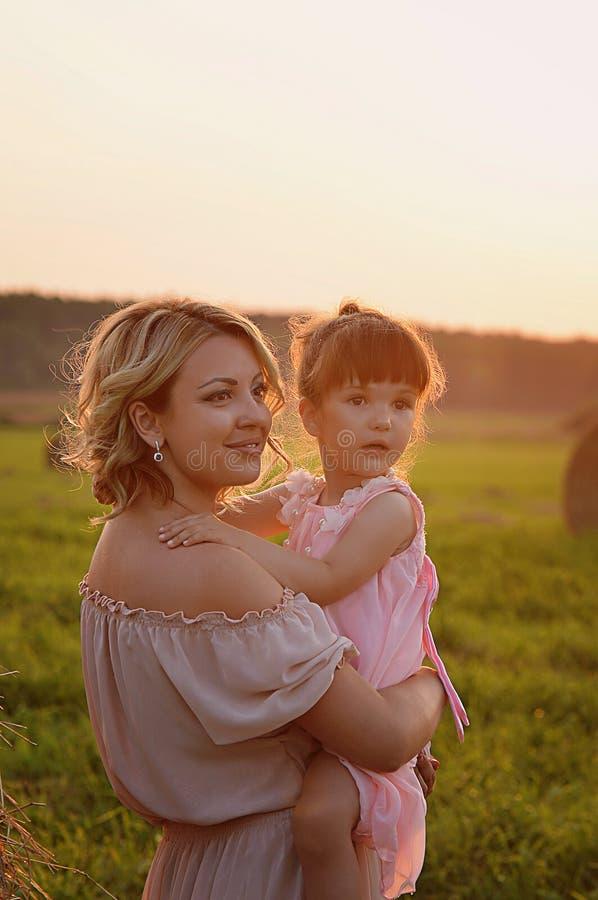 Мать и дочь в этих же вводят поле в моду, свет захода солнца Нежность стоковая фотография