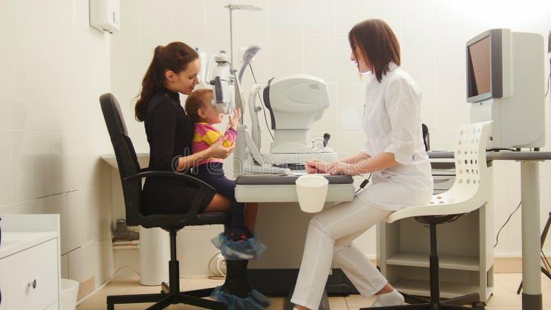 Мать и дочь в optometrist комнаты ` s офтальмолога в клинике проверяя зрение ` s маленького ребенка стоковое фото
