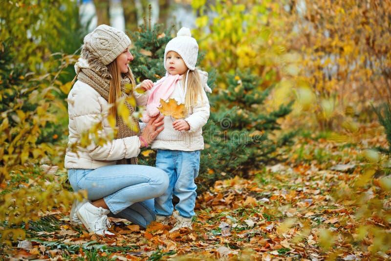 Мать и дочь гуляя в парк осени стоковые фотографии rf