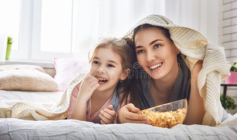Мать и дочь есть попкорн стоковые фотографии rf