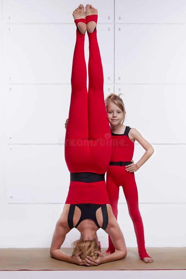 Мать и дочь делая йогу работают, фитнес, pai спорт спортзала стоковая фотография