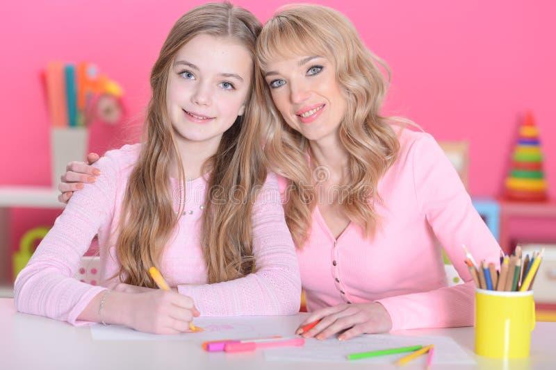 Мать и дочь делая уроки стоковое изображение