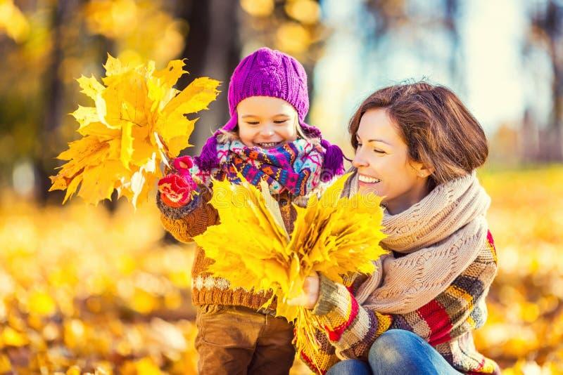 Мать и дочь играя в парке осени стоковые изображения rf