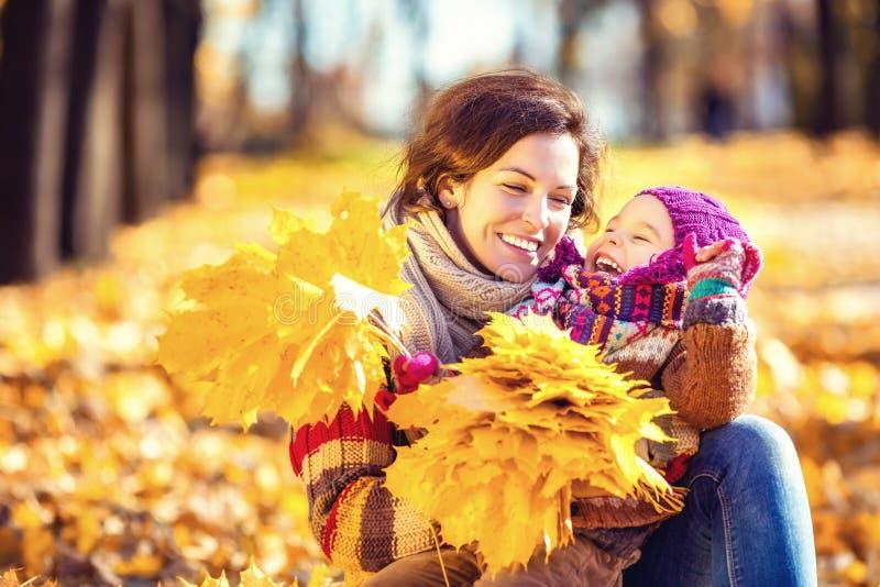 Мать и дочь играя в парке осени стоковое фото rf