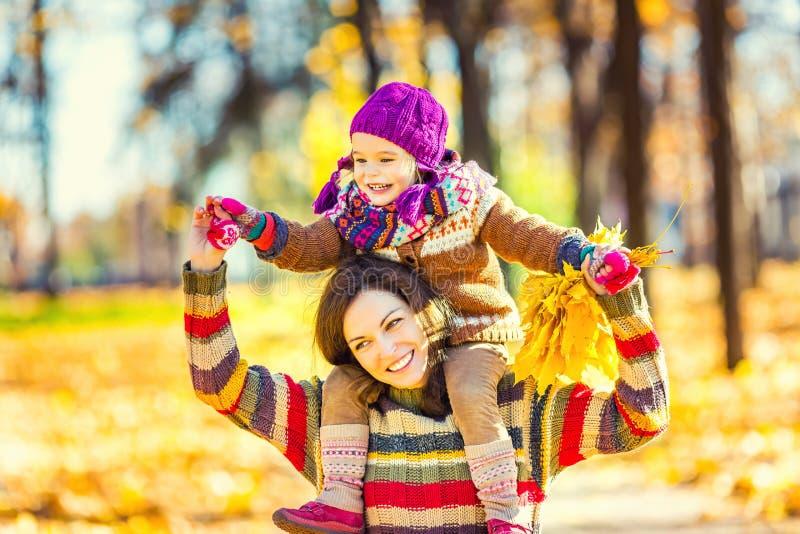 Мать и дочь играя в парке осени стоковая фотография rf