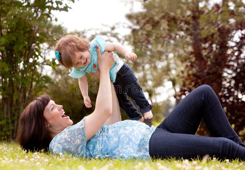 Мать и дочь играя в парке стоковое изображение