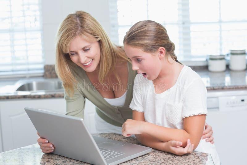 Мать и дочь используя компьтер-книжку совместно стоковые фото