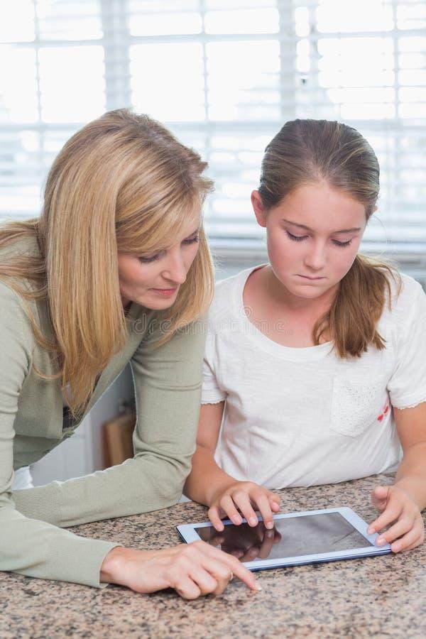 Мать и дочь используя ПК таблетки совместно стоковые фотографии rf