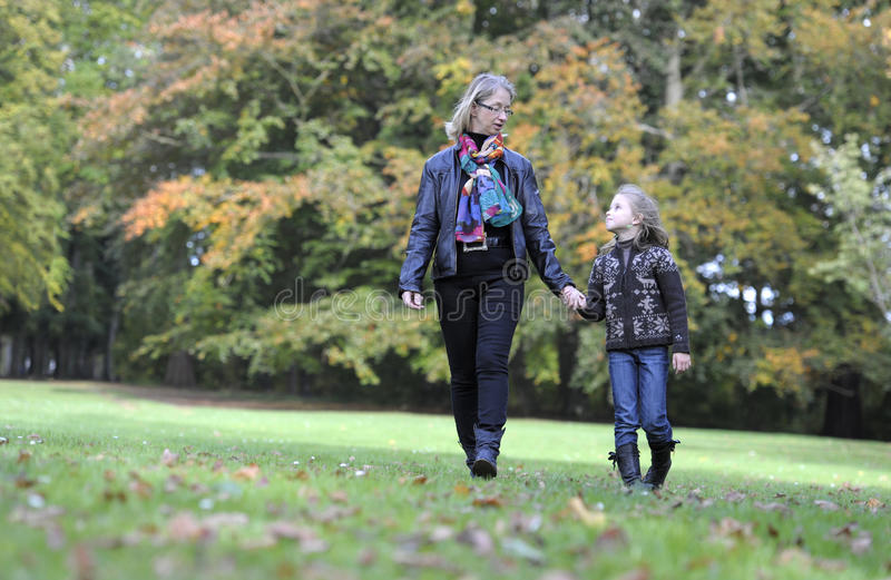 Мать и дочь идя в парк стоковые фотографии rf