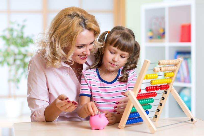 Мать и дочь кладя монетки в piggy банк стоковые фотографии rf