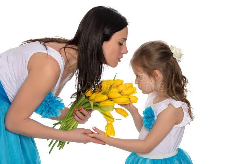 Мать и дочь пахнуть желтыми тюльпанами стоковая фотография rf