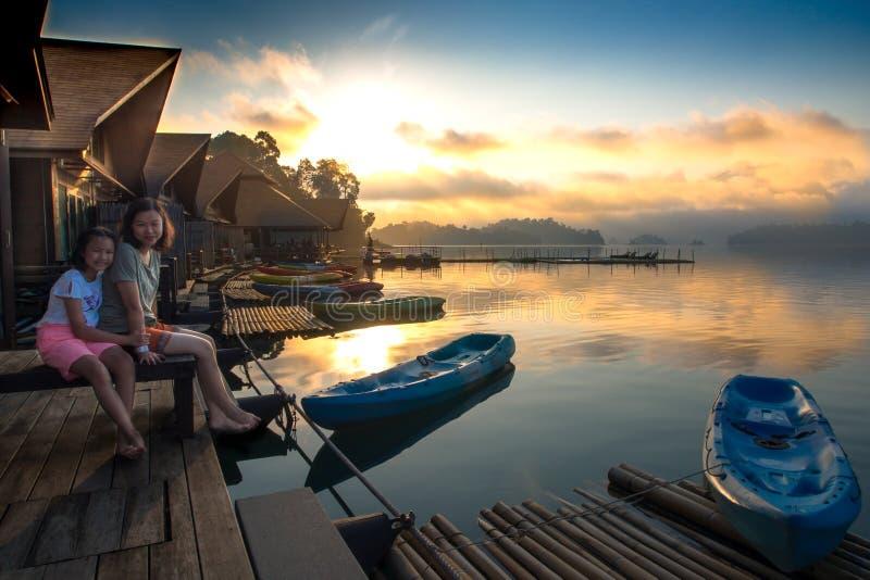 Мать и дочь сидя на озере сплотка естественном в утре стоковое изображение rf
