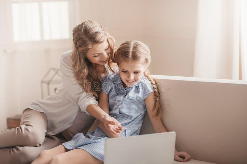 Мать и дочь сидя на софе и используя компьтер-книжку дома стоковое фото rf