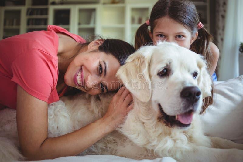 Мать и дочь сидя с собакой в живущей комнате стоковая фотография rf