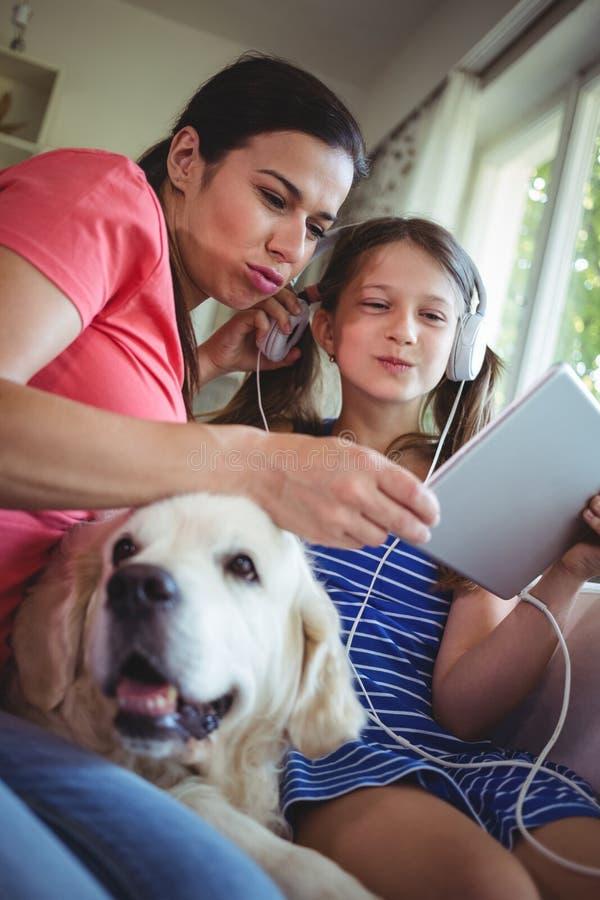 Мать и дочь сидя с собакой и использование цифровое стоковое фото rf