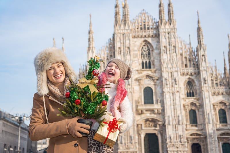Мать и дочь с рождественской елкой и подарком в милане стоковое изображение rf