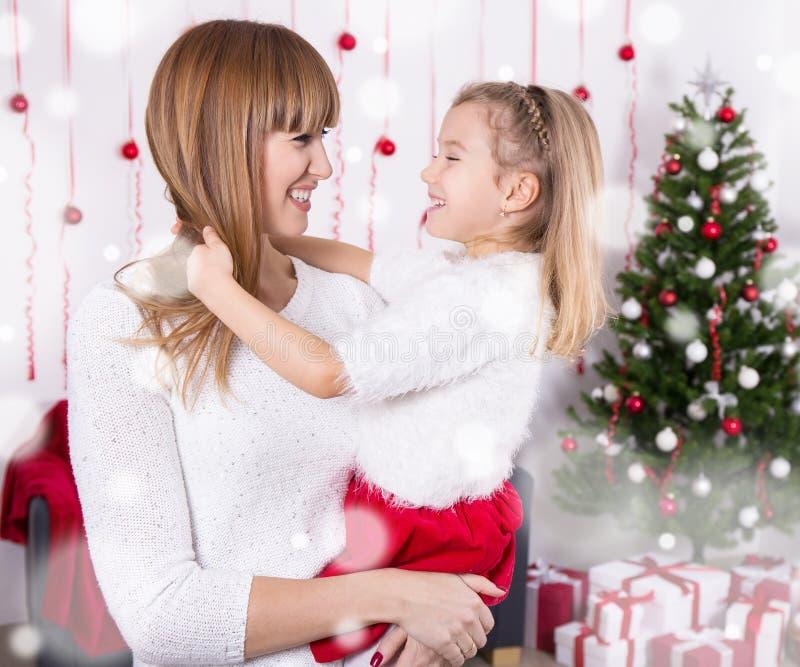 Мать и дочь с рождественской елкой дома стоковое фото rf