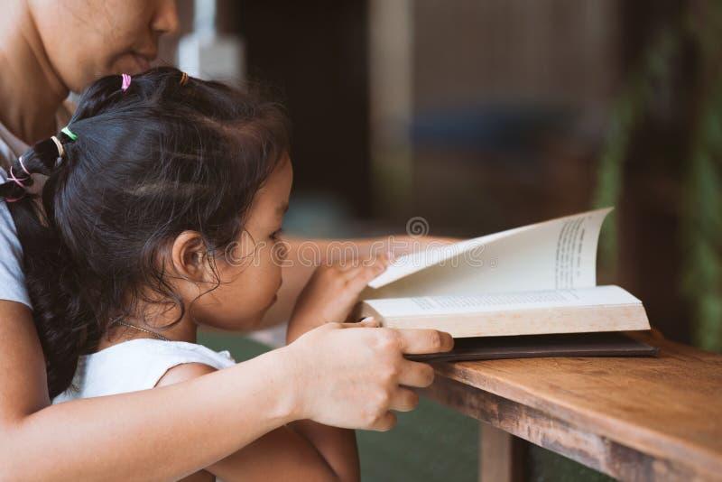 Мать и дочь читая книгу совместно стоковое изображение rf