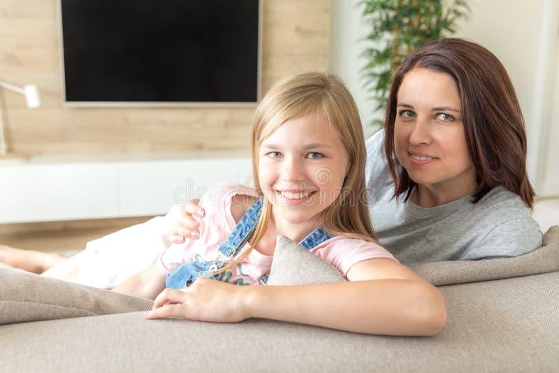 Мать и пре-предназначенная для подростков дочь сидя на усмехаться кресла r стоковое фото
