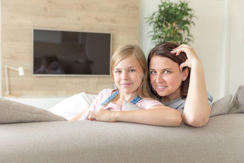 Мать и пре-предназначенная для подростков дочь сидя на усмехаться кресла r стоковые фото