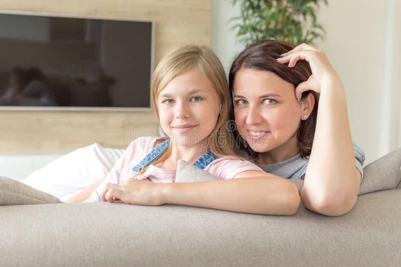 Мать и пре-предназначенная для подростков дочь сидя на усмехаться кресла r стоковое изображение rf