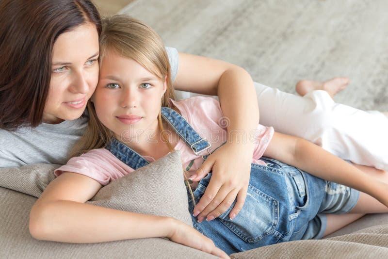 Мать и пре-предназначенная для подростков дочь сидя на усмехаться кресла r стоковые изображения
