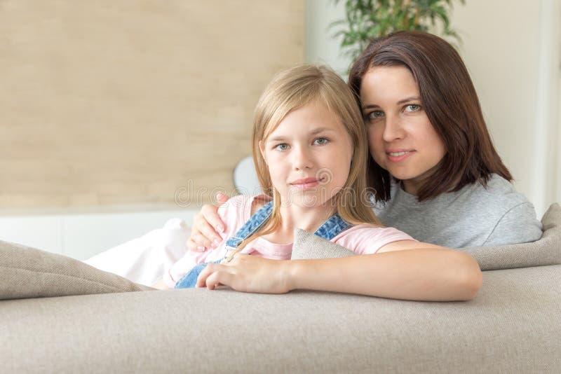 Мать и пре-предназначенная для подростков дочь сидя на усмехаться кресла r стоковое изображение